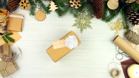 сосновая шишка : Woman female adult stealing take away christmas box gift with bow ribbon on white wooden background with new year christmas decorations and pine tree . Merry Christmas and Happy New Year concept.