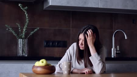 napětí : Woman person housewife sitting in modern gray interior kitchen home has headache migraine depression stress cold flu pain illness disease symptom. Unhealthy lifestyle health care suffering concept Dostupné videozáznamy