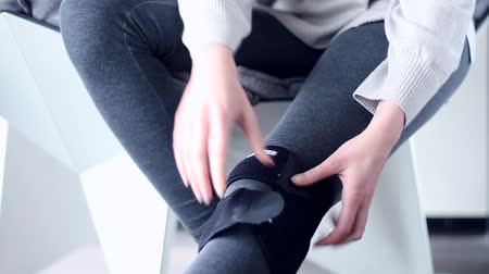 stabilizátor : Woman person sitting in modern gray interior chair, put medical elastic knee brace on leg and walk in it. Sprains muscle ligament knee damage, crick, unhealthy stress lifestyle, health care, concept.