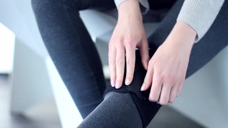 ayarlanabilir : Woman person sitting in modern gray interior chair, tightens the medical elastic knee brace bandage on leg. Sprains muscle ligament broken knee damage, crick, unhealthy injury rehabilitation concept.