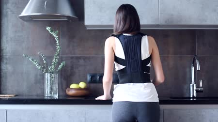 espartilho : Back view of young slim woman dressed in back support bandage is cleaning kitchen. Brunette girl straightens her back with corset for posture correction. Backbone disease therapy and treatment concept