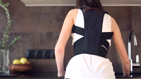 backbone : Back view of young slim woman dressed in back support bandage is cleaning kitchen. Brunette girl straightens her back with corset for posture correction. Backbone disease therapy and treatment concept