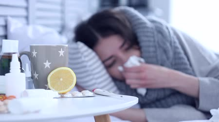 durgunluk : Beautiful sick ill woman female adult with scarf lying on bed with flu at grey bedroom with medicine, drugs and cup of tea with lemon against cold. Coughing and sneezing. Health issue concept. Stok Video