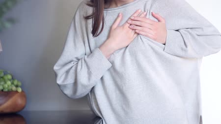 острый : Beautiful female adult woman in grey cloth has acute pain in thoracic, heart attack or health issue. Massing chest and suffering from pain at kitchen. Heart health concept.