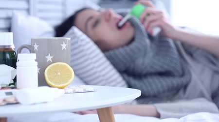 fájó : Beautiful sick ill woman female adult with scarf lying on bed with flu at grey bedroom with medicine, drugs and cup of tea with lemon, taking medicine against sore throat. Health issue concept. Stock mozgókép