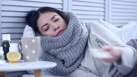 durgunluk : Beautiful sick ill woman female adult with scarf lying on bed with flu at grey bedroom with medicine, drugs and cup of tea with lemon, taking pill against cold. Health issue, flu and cold concept.