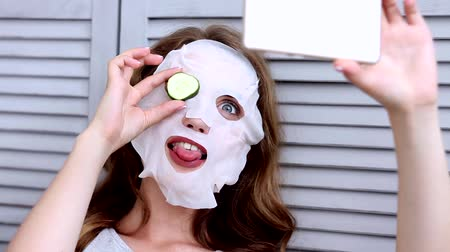 regenerating : Happy smiling woman with Korean sheet fabric fiber pulp face clean mask with cucumber on eye do selfie Girl morning routine. Beauty young skin care anti-aging anti-wrinkle concept natural botox effect Stock Footage