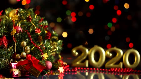 çelenk : Gold inscription 2020, decorated wreath, presents, decor are on table. Festive decorative garland with multicolored light bulbs, lanterns are blinking on background. New year, christmas mood. Stok Video