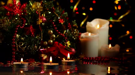 çelenk : Candles are burning, decorated wreath, decor for christmas tree, presents, balls are on table. Festive decorative garland with multicolored light bulbs are shining on background. New year mood.