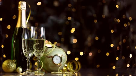 полночь : Glasses with champagne, new year golden decor, balls are on table. Clock is ticking, few minutes to midnight. Festive decorative garland, warm yellow light bulbs are blinking on background. Стоковые видеозаписи