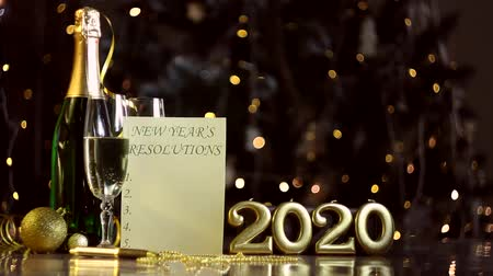 liste : Bottle, glasses with champagne, gold decor, balls, pen, paper with list of new year resolutions, inscription candles 2020 on table. Festive garland, yellow light bulbs are blinking on background.