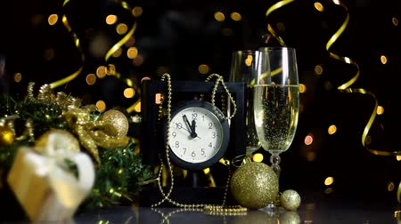 ticking : Glasses with champagne, New Year golden decor, balls are on table. Black clock is ticking, few minutes to midnight. Festive decorative garland, warm yellow light bulbs are blinking on background. Stock Footage