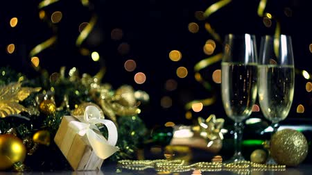 kabarcıklı : Two glasses with champagne, New Year golden decor for christmas tree, balls, present are on table. Serpentine, festive decorative garland, warm yellow light bulbs are blinking on background.