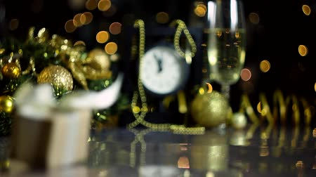 çelenk : Glasses with champagne, present box, decorated wreath, new year balls on table. Clock is ticking, few minutes to midnight. Festive decorative garland, yellow light bulbs are blinking on background.