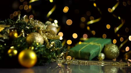 çelenk : Decorated wreath, gold decor for christmas tree, balls, present box wrapped in green paper are on table. Serpentine, festive decorative garland, warm yellow light bulbs are blinking on background. Stok Video