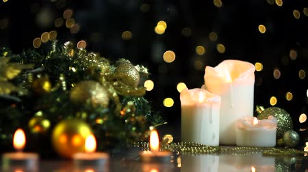 çelenk : White candles are burning, decorated wreath, gold decor for christmas tree, balls are on table. Festive decorative garland, warm yellow light bulbs, lanterns are blinking on background. New year mood. Stok Video