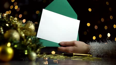 gratulací : Female hands are opening green envelope with blank sheet of paper for greeting card. Decorated wreath, decor for christmas tree, balls are on table. Garland with yellow light bulbs are blinking.