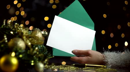 çelenk : Female hands are opening green envelope with blank sheet of paper for greeting card. Decorated wreath, decor for christmas tree, balls are on table. Garland with yellow light bulbs are blinking.