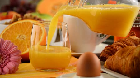 meyve suyu : Filling glass with orange juice on table with breakfast