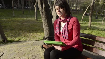 pensamento : Beautiful, brown hair, green eye, red, pink sweater, cardigan, scarf woman is thinking, sitting, holding a green tablet at a public garden, park, sunny day
