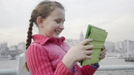 obrázky : Little, blonde, ponytail, white skin, pink jacket, girl is taking picture, photograph with a green tablet at Istanbul, Galata Tower and Bridge