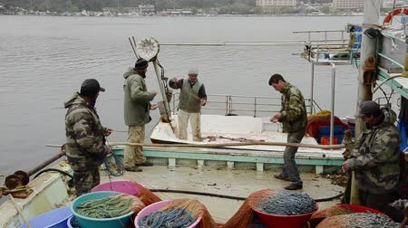 hooker : 14 April, 2013, Sile, Istanbul: Professional Fishermans are repairing their fishnet, fishing net together on landed fishing boat.