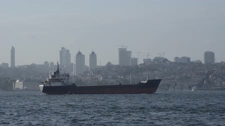 партия : Small tanker is crossing the Bosporus Edge on a foggy weather silhouette of Galata Tower at Istanbul