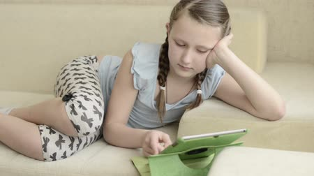 teenager : Little blonde ponytail white skinned girl playing using looking green tablet computer on a cream color couch sofa bed when she is lie down. She is standing her elbow to the couch.