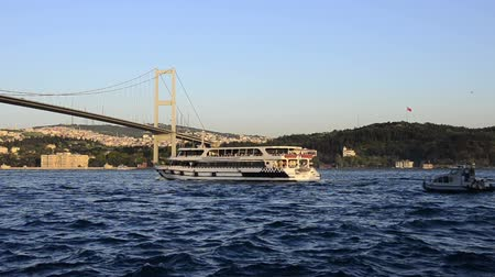 освещать : Bosphorus Bridge is always most touristic area of Istanbul it is always possible to see small boats pass under  of the bridge. Стоковые видеозаписи