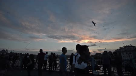 sociedade : Time lapse timelapse shoot of people silhouette on Galata Bridge Istanbul on sunset. Community urban Profile view.  Recreational region fisherman are hunting fish front of banisters. Lateral view.