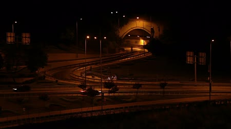 honit : Cars are passing on freeway where behind of a tunnel gate at night.