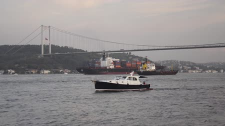 przesyłka : Black boarded small yacht and two container ships crossing Bosporus strait and Bosphorus Bridge at Istanbul Wideo