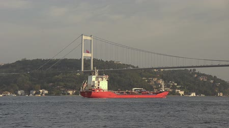 przesyłka : Small red tanker ship is cruising and crossing the Bosphorus Bridge on sunset