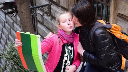 csók : Beautiful tourist mom and her daughter taking selfie with tablet on street