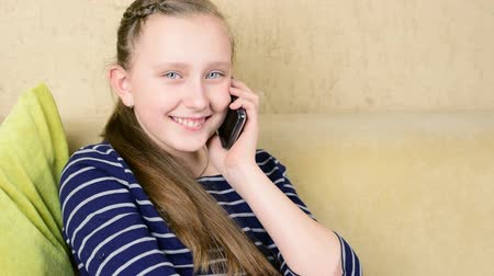 teenager : Beautiful teenage blue eyed blonde girl talk on phone on sofa close up isolated portrait Stock Footage