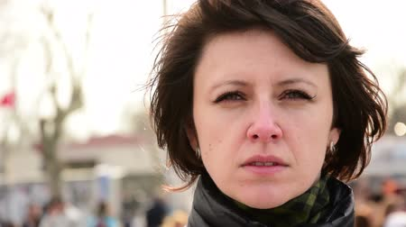 crows feet : Close up portrait of sad beautiful brunette woman on street on windy weather.