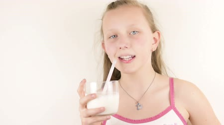 imitação : Beautiful teenage blue eyed blonde girl drinking milk by straw from a glass close up isolated