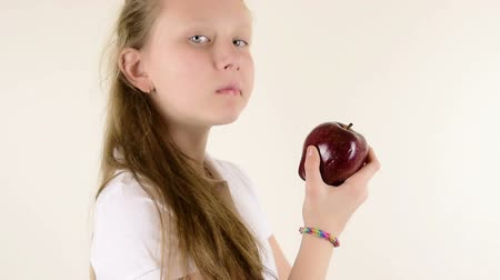 tizenéves lányok : Beautiful teenage blue eyed blonde girl eating red apple close up isolated studio