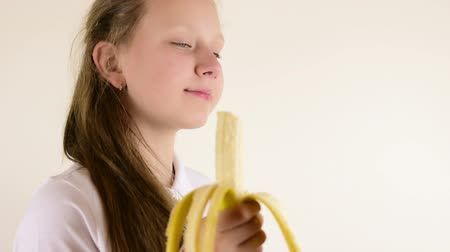 muz : Beautiful teenage blue eyed blonde girl eating banana close up isolated studio