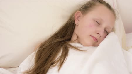 cobertor : Beautiful big blue eyed teenage girl fall asleep on white bed close up