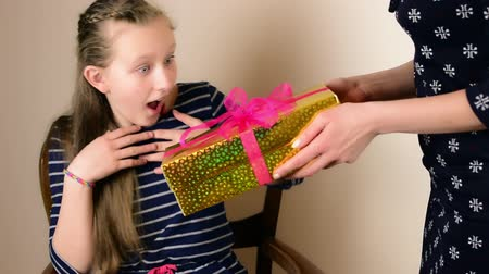 csók : Beautiful blue eyed blonde teenage girl receive golden gift box from her mom close up isolated studio