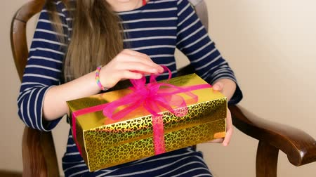 den matek : Woman receive golden gift box and inspecting it on her lap Dostupné videozáznamy