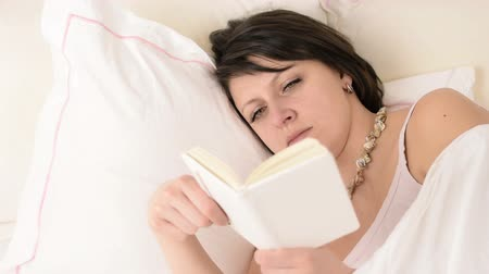 crows feet : Beautiful big green eyed brunette woman is reading before fall asleep on white bed portrait