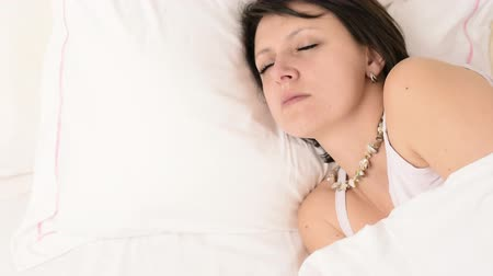 crows feet : Beautiful big green eyed brunette woman fall asleep on a white bed portrait