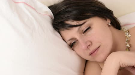 beauty spot : Beautiful big green eyed brunette woman fall asleep on a white bed portrait close up