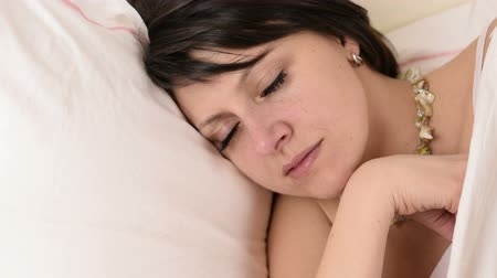 crows feet : Beautiful big green eyed brunette woman fall asleep on a white bed portrait close up