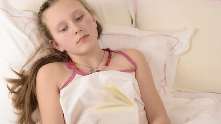 sarışın : Beautiful big blue eyed teenage girl read book on white bed close up Stok Video