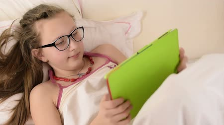 tizenéves lányok : Blonde beautiful black glasses teenage girl play with tablet on white bed Stock mozgókép