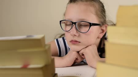uykulu : Tired blue eyed black glasses school girl is sleeping studying lesson on a wood table