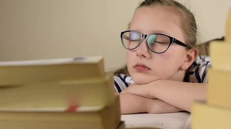 aluno : Tired blue eyed black glasses school girl is sleeping studying lesson on a wood table